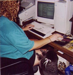 Pet Groomer sitting at computer using Groomer's Write Hand